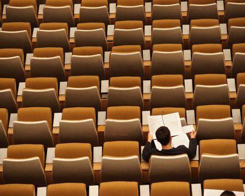 Lernender Schüler zwischen vielen leeren Schulen